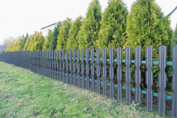 Przykład ogrodzenia z tworzywa Obraz za https://ogrodzeniaplastikowe.pl/galeria-sztachet-korner/